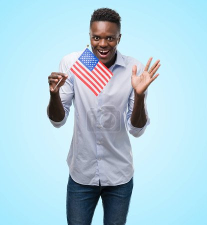 Photo for Young african american man holding USA flag very happy and excited, winner expression celebrating victory screaming with big smile and raised hands - Royalty Free Image