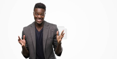 Photo pour Jeune homme afro-américain vêtu d'une veste très heureuse et excitée, expression gagnante célébrant la victoire en criant avec un grand sourire et les mains levées - image libre de droit