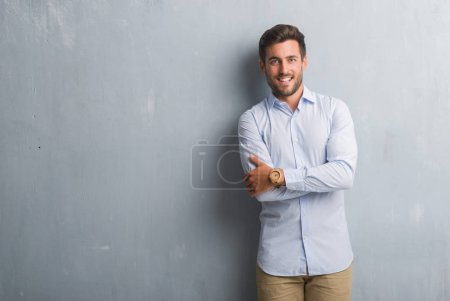 Photo for Handsome young business man over grey grunge wall wearing elegant shirt happy face smiling with crossed arms looking at the camera. Positive person. - Royalty Free Image