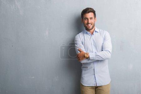 Foto de Hombre de negocios joven guapo sobre pared gris grunge elegante camisa feliz cara sonriente con los brazos cruzados, mirando a la cámara. Persona positiva. - Imagen libre de derechos