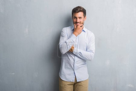 Handsome young business man over grey grunge wall wearing elegant shirt looking confident at the camera with smile with crossed arms and hand raised on chin. Thinking positive.