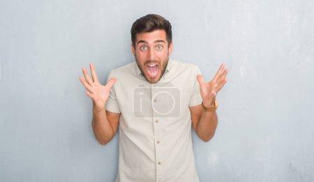 Photo pour Beau jeune homme sur le mur gris grunge portant chemise d'été célébrant fou et étonné pour le succès avec les bras levés et les yeux ouverts hurlant excités. Concept gagnant - image libre de droit