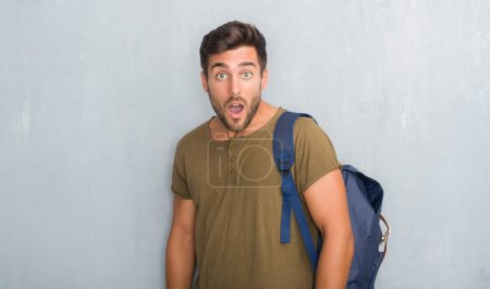Handsome tourist young man over grey grunge wall wearing backpack afraid and shocked with surprise expression, fear and excited face.