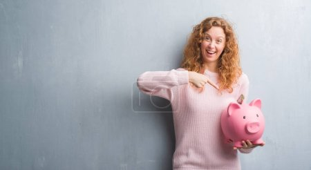 Young redhead woman over grey grunge wall holding piggy bank and dollar very happy pointing with hand and finger