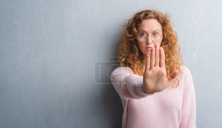 Photo pour Femme jeune rousse sur mur gris grunge, portez des lunettes avec une main ouverte faisant signe d'arrêt avec l'expression grave et confiante, geste de défense - image libre de droit