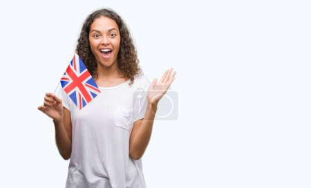 Young hispanic woman holding flag of United Kingdom very happy and excited, winner expression celebrating victory screaming with big smile and raised hands