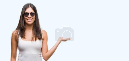 Jeune hispanique de belles lunettes de soleil sourire joyeux présentant et en pointant avec la paume de la main en regardant la caméra