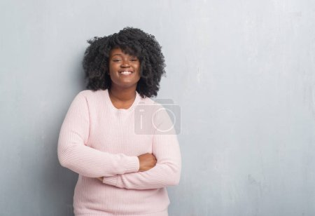 Young african american plus size woman over grey grunge wall wearing winter sweater happy face smiling with crossed arms looking at the camera. Positive person.