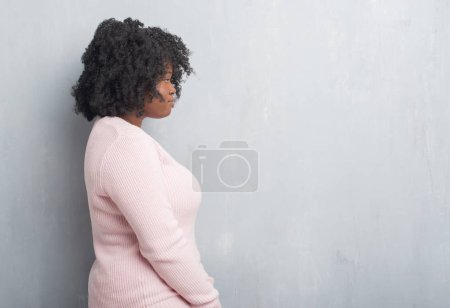 Young african american plus size woman over grey grunge wall wearing winter sweater looking to side, relax profile pose with natural face with confident smile.