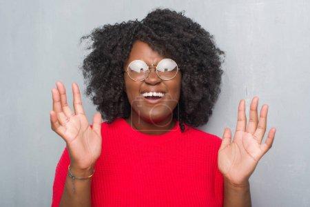 Photo pour Jeune femme afro-américaine au fil gris grunge mur portant pull hiver et verres fou et folle criant et hurlant avec expression agressive et bras levés. Concept de frustration. - image libre de droit