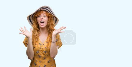 Young redhead woman wearing summer hat and dress very happy and excited, winner expression celebrating victory screaming with big smile and raised hands