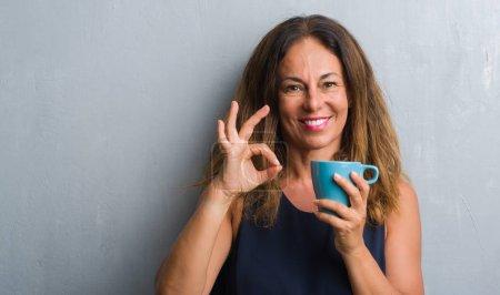 Photo pour Moyen Age femme hispanique debout sur le mur gris grunge boire tasse de café faire ok signe avec les doigts, excellent symbole - image libre de droit