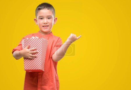 Photo for Dark haired little child eating popcorn very happy pointing with hand and finger to the side - Royalty Free Image