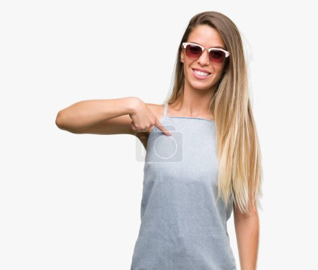 Beautiful young woman wearing sunglasses and denim dress with surprise face pointing finger to himself