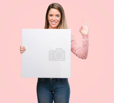Beautiful young woman holding advertising banner doing ok sign with fingers, excellent symbol