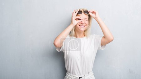 Adult caucasian woman over grunge grey wall wearing sunglasses doing ok gesture with hand smiling, eye looking through fingers with happy face.
