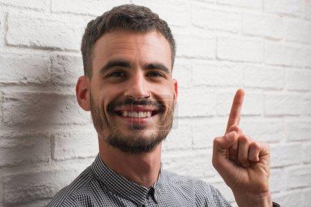 Jeune homme adulte debout sur un mur de briques blanches surpris par une idée ou une question pointant du doigt avec un visage heureux, numéro un