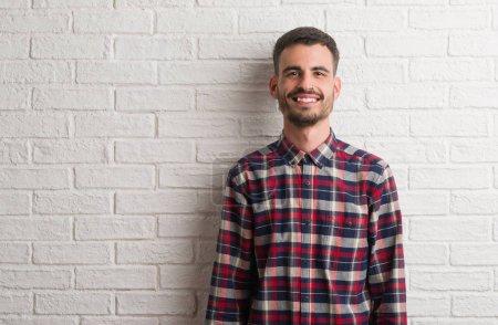 Jeune homme adulte debout sur un mur de briques blanches avec un sourire heureux et cool sur le visage. Personne chanceuse .