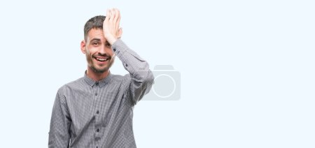 Young hipster man surprised with hand on head for mistake, remember error. Forgot, bad memory concept.