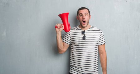 Young caucasian man over grey grunge wall shouting trough megaphone scared in shock with a surprise face, afraid and excited with fear expression