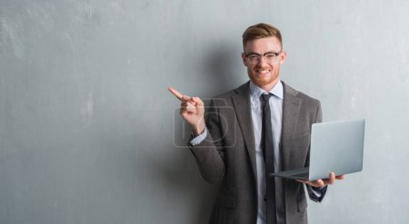 Photo for Young redhead elegant business man over grey grunge wall using laptop very happy pointing with hand and finger to the side - Royalty Free Image
