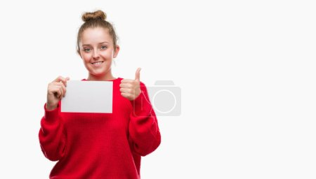 Young blonde woman holding advertising banner happy with big smile doing ok sign, thumb up with fingers, excellent sign