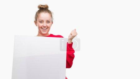 Photo pour Jeune femme blonde, tenant la bannière publicitaire crier fier et célébrant la victoire et le succès très excité, acclamant l'émotion - image libre de droit