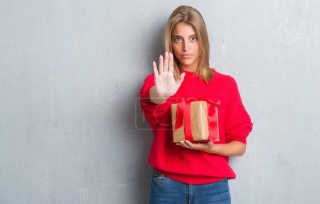 Photo pour Belle jeune femme sur mur gris grunge tenant dans l'amour d'un cadeau avec la main ouverte, faisant signe d'arrêt avec l'expression grave et confiante, geste de défense - image libre de droit