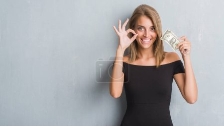 Beautiful young woman over grunge grey wall holding a dollar doing ok sign with fingers, excellent symbol