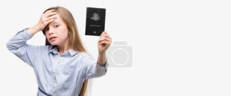 Young blonde toddler holding australian passport stressed with hand on head, shocked with shame and surprise face, angry and frustrated. Fear and upset for mistake.