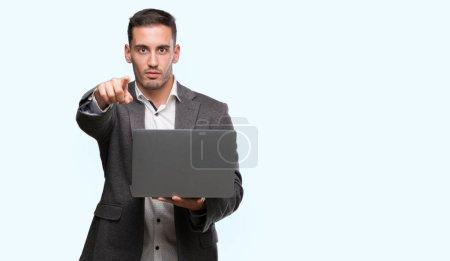 Photo pour Beau jeune homme utilisant ordinateur portable pointant du doigt vers la caméra et à vous, signe de la main, geste positif et confiant de l'avant - image libre de droit