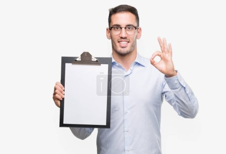 Handsome young business man showing a clipboard doing ok sign with fingers, excellent symbol