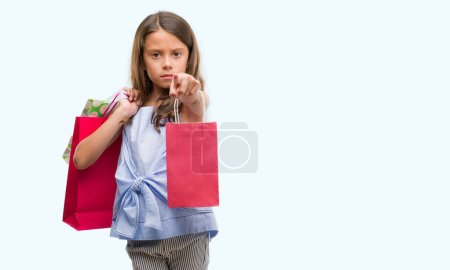 Brunette hispanic girl holding shopping bags pointing with finger to the camera and to you, hand sign, positive and confident gesture from the front