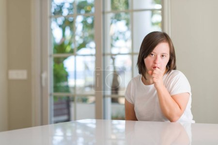 Down syndrome woman at home feeling unwell and coughing as symptom for cold or bronchitis. Healthcare concept.