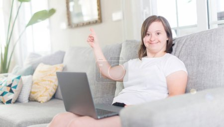 Down syndrome woman at home using computer laptop very happy pointing with hand and finger to the side