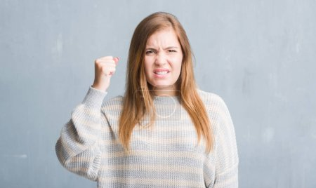 Young adult woman over grey grunge wall annoyed and frustrated shouting with anger, crazy and yelling with raised hand, anger concept