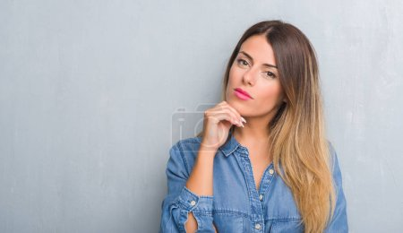 Young adult woman over grunge grey wall wearing denim outfit with hand on chin thinking about question, pensive expression. Smiling with thoughtful face. Doubt concept.