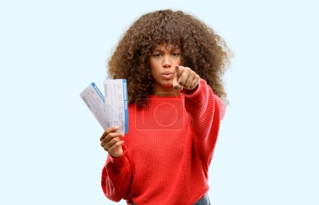 Photo for African american woman holding airline boarding pass tickets pointing with finger to the camera and to you, hand sign, positive and confident gesture from the front - Royalty Free Image
