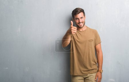 Photo for Handsome young man over grey grunge wall doing happy thumbs up gesture with hand. Approving expression looking at the camera with showing success. - Royalty Free Image