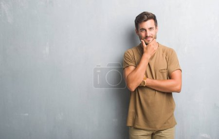Handsome young man over grey grunge wall looking confident at the camera with smile with crossed arms and hand raised on chin. Thinking positive.