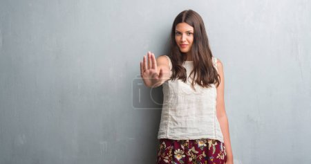 Photo pour Jeune femme brune sur mur gris grunge avec main faisant signe d'arrêt avec l'expression grave et confiante, geste de défense ouverte - image libre de droit