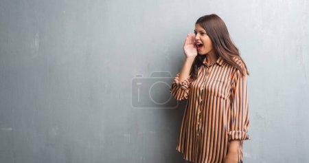 Photo pour Jeune femme brune sur un mur gris grunge criant et criant fort à côté avec la main sur la bouche. Concept de communication . - image libre de droit
