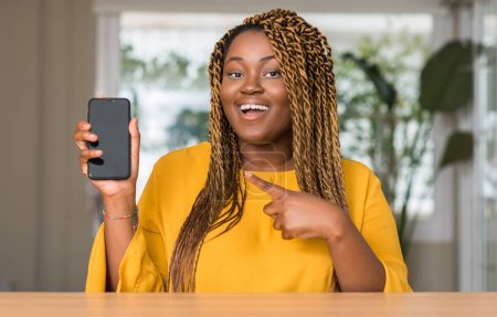 Photo for African american woman using smartphone very happy pointing with hand and finger - Royalty Free Image