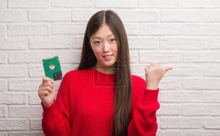 Photo pour Jeune femme chinoise sur mur de brique comprenant disque dur pointant et montrant avec le pouce jusqu'à la face visage heureux souriant - image libre de droit