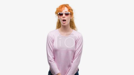 Young redhead woman wearing sunglasses scared in shock with a surprise face, afraid and excited with fear expression