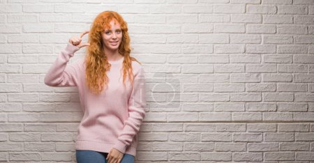 Young redhead woman standing over brick wall smiling and confident gesturing with hand doing size sign with fingers while looking and the camera. Measure concept.