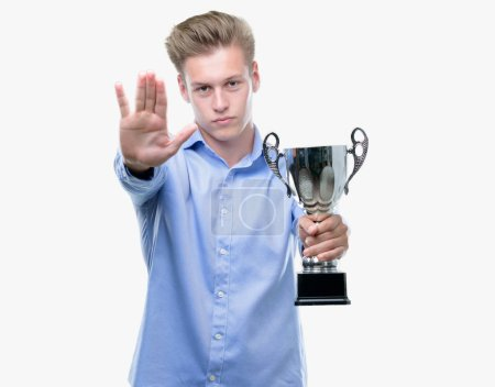 Photo pour Jeune bel homme blond tenant un trophée avec main faisant signe d'arrêt avec l'expression grave et confiante, geste de défense ouverte - image libre de droit