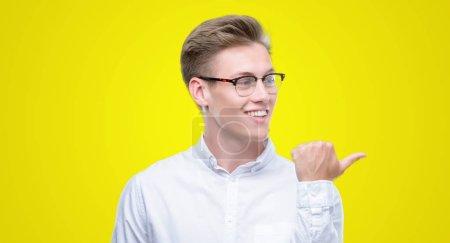 Photo pour Jeune homme blond beau sourire avec le visage heureux regardant et pointant vers le côté avec le pouce vers le haut . - image libre de droit