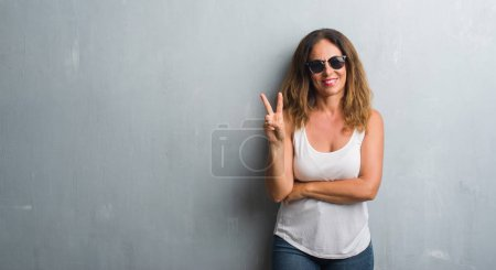 Photo for Middle age hispanic woman over grey wall wearing sunglasses smiling with happy face winking at the camera doing victory sign. Number two. - Royalty Free Image