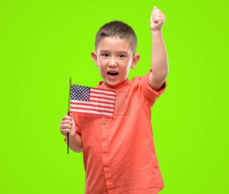 Dark haired little child holding United States flag annoyed and frustrated shouting with anger, crazy and yelling with raised hand, anger concept